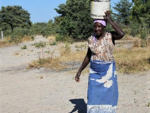 Sepiso Mulonda of the Kapau community carrying bucket of water on her head