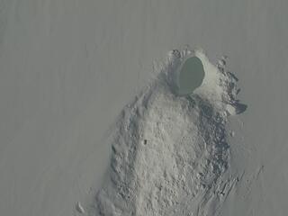Image of an empty polar bear den in a snowy landscape