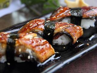Three pieces of unagi sushi on a black platter