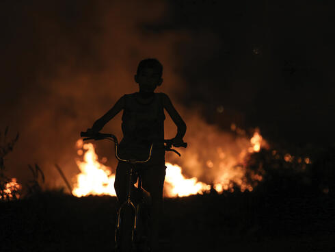 Child on bike silhouetted by fire in background