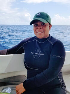 Photo of Nadia Bood, who is smiling on a small research boat