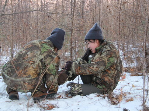 Two female rangers sit in the forest while one helps the other remove her foot from a snare