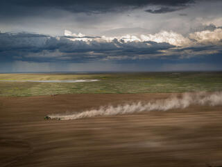A tractor plows a vast field with a rain storm in the distant background