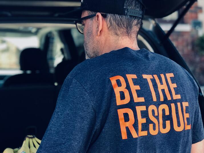"A man in a ""Be the Rescue"" t-shirt unloads bananas from the back of a car"