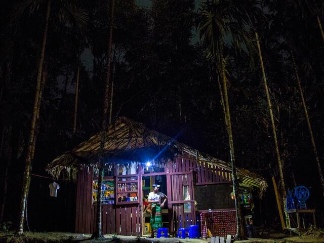 Illuminated village shop in dark landscape
