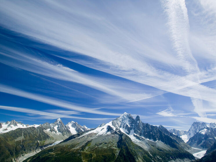 Tall mountains with blue sky above. White vapor trails streak across the blue sky.