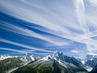 Tall mountains with blue sky above. White vapor trails streak across the blue sky.