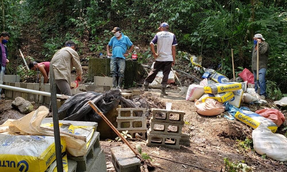A group of Honduran men in a forest surrounded by bags of concrete and other materials to build a new water system