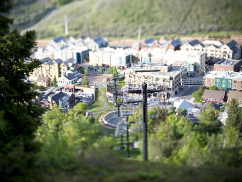 Houses and a ski lift set in a green forested area.