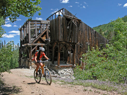 A person rides a bike on a dirt path, with an abandoned cabin in the background.