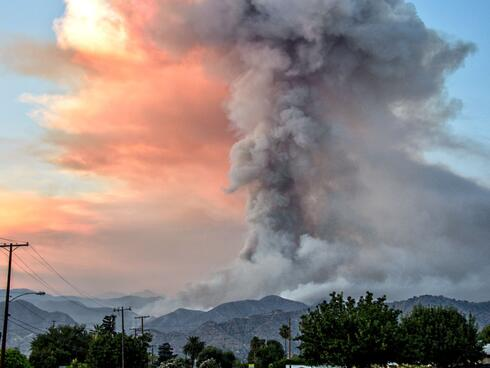 A tower of smoke rises from a wildfire.