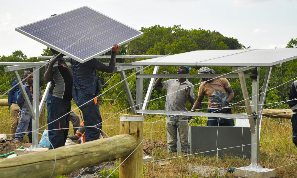 A group of men working together to assemble solar panels in a field