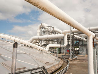 large pipes leading from a biogas tank to a processing plant