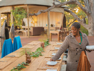 Catherine Mafumelo sets plates on an outdoor table