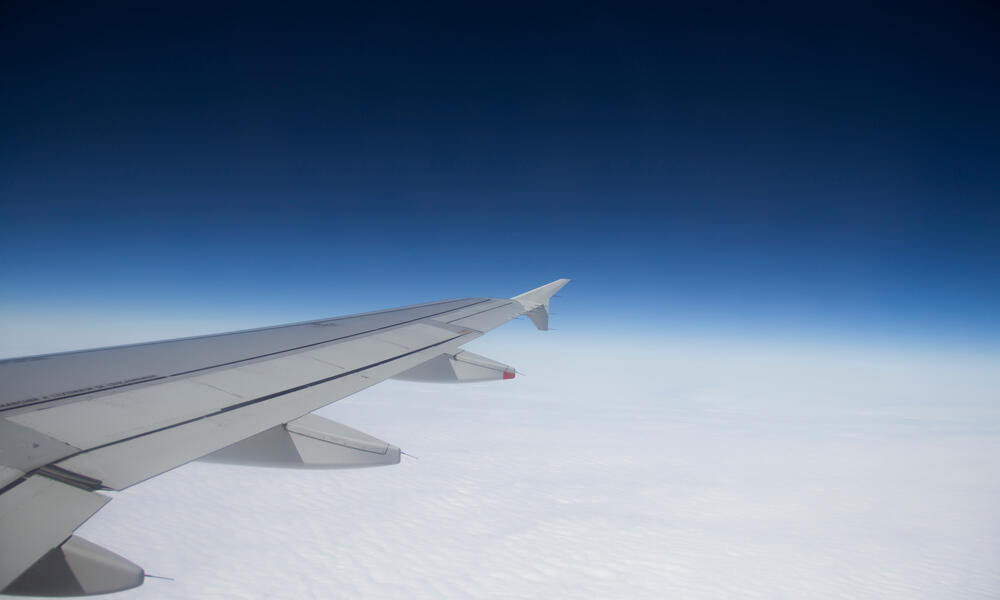 Airplane wing against the background of clouds and sky