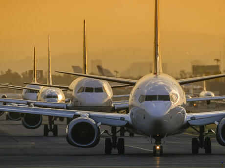 Airplanes in line to take off at sunset