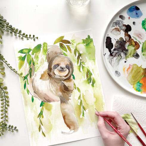 Photo of a painting of a sloth on a table with palette and artist's hand