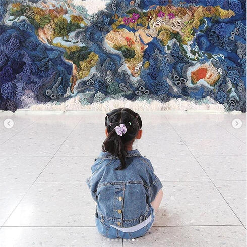 Photo of girl seated looking at mural