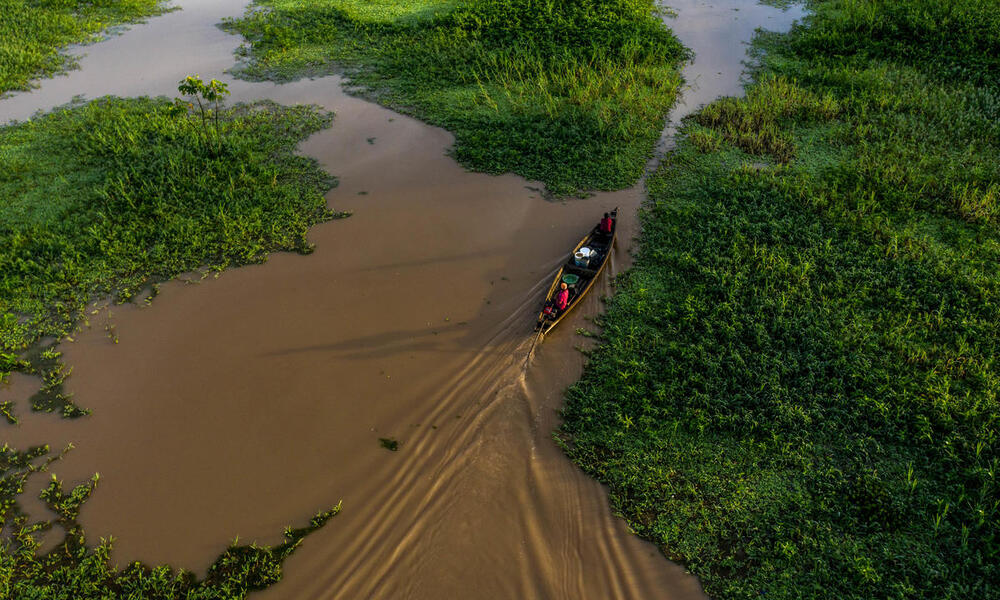 Two people drive a small boat through muddy waters and green marshland