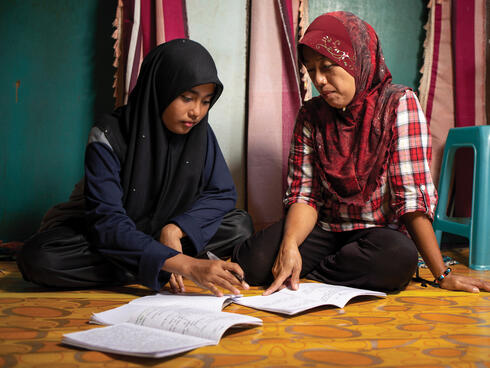 Girls in headscarves work on studies