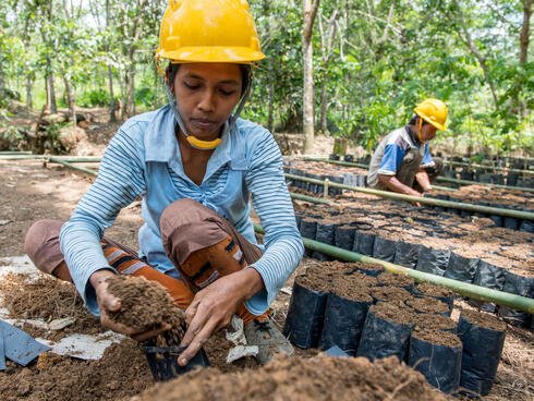 A woman in a blue top and yellow hard hat kneels down to fill black potting bags with soil