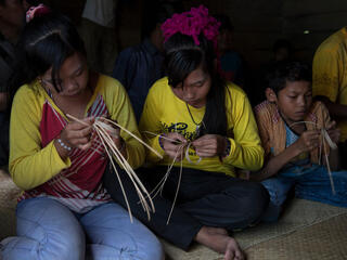 Two women and a small boy sit on the floor weaving crafts