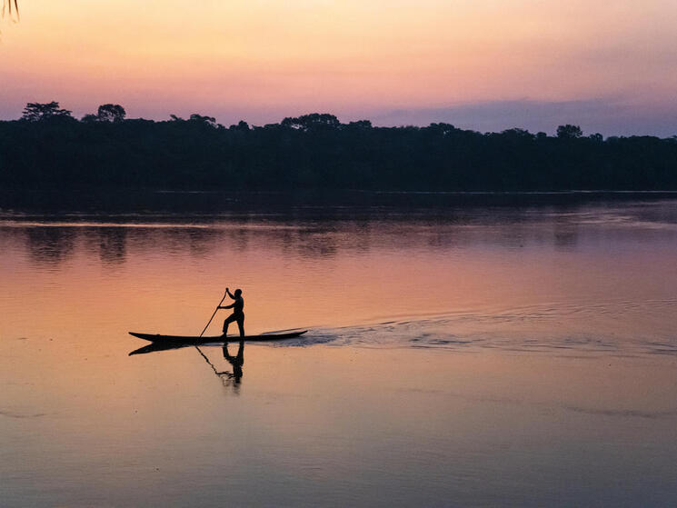 Someone standing up paddling on a slim canoe along a river at sunset with pink and purple hues
