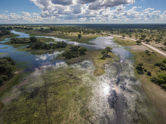 Aerial view of flood water arriving to the Okavango Delta, Botswana under blue cloudy skies