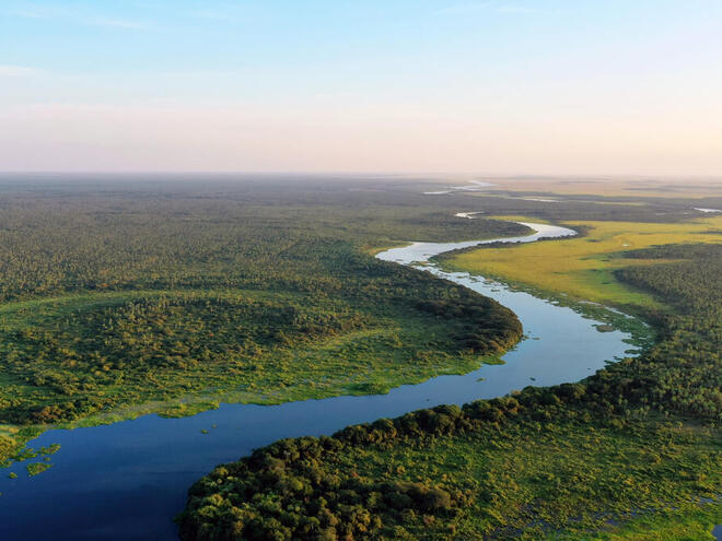 Aerial view of a blue river snaking through green lands