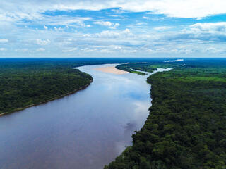 Aerial view of a free-flowing blue river snaking through the green Bolivian Amazon