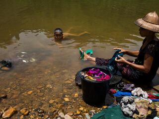 A woman sits on a river bank washing clothes while a child swims naked in the water