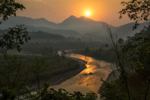 A lush landscape in Nepal with mountains in the background and a winding river at sunrise