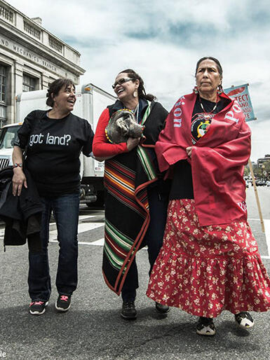 Three Indigenous women walk arm in arm down a main road in Washington, DC at the People's Climate March.