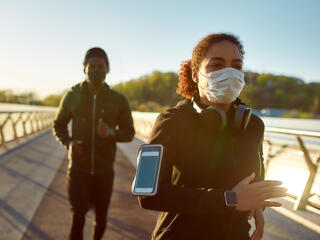 Two people running outside with face masks