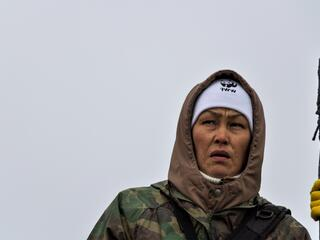 Portrait of a woman wearing a camoflauge jacket and carrying a spear