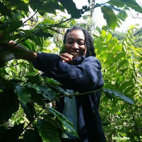 Alexa White smiles while surrounded by lush greenery