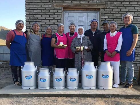 A group of people wearing blue or pink aprons and hair nets stand in a row smiling at the camera behind a row of metal milk jugs