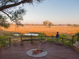 A person stands on a wood deck of Nambwa Lodge, looking out towards the savannah.