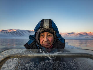 A man wearing a thick blue parka looks into the camera. He is on a boat at sunrise. Behind him is snow covered land.