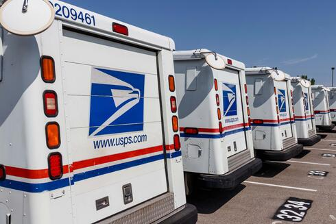 A row of US Postal trucks lined up in a parking lot