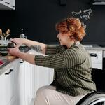 A woman in a wheelchair chops vegetables