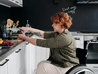 A woman in a wheelchair chops vegetables