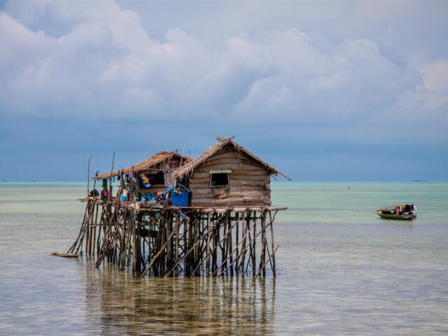 Small woven houses sitting on top of a system of stilts out in clear blue water with a green boat anchored nearby