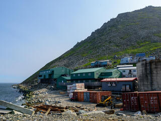 A small seaside village with houses on the shore and a large rocky hill directly behind them