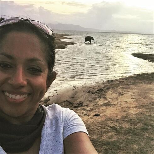 Nilanga Jayasinghe smiling at the camera in front of water with an elephant walking by