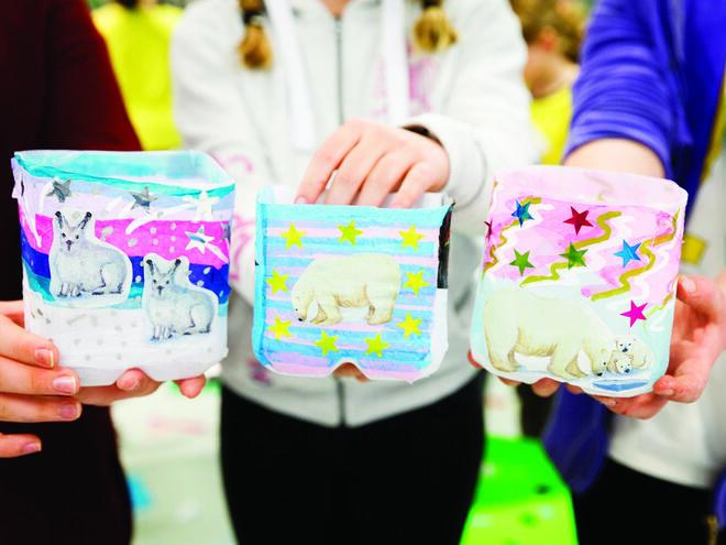 Three individuals holding completed polar bear lantern crafts