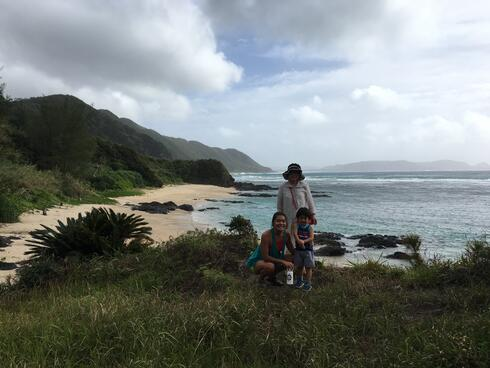 Ellie Yanagisawa kneels next to her nephew. Her grandma stands behind them. They all are on a beach in Amami.