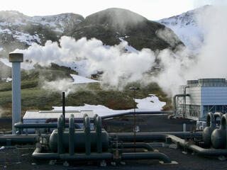 Smoke emits from a pipe at a hydrogen production plant with mountains in the background