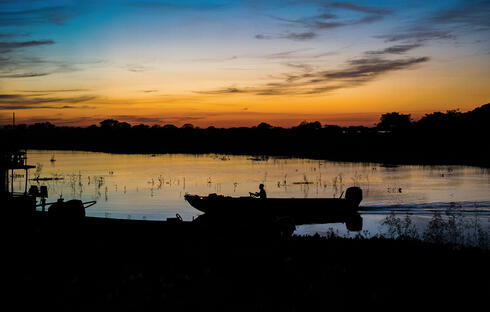 Sunset along river with canoe silhouette