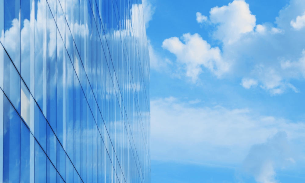 glass office building blue sky and clouds